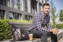 Человек, сидящий на скамейке с кофе — стоковое фото