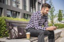 Uomo seduto sul banco e messaggi di testo — Foto stock