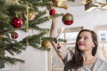 Woman decorating Christmas tree — Stock Photo