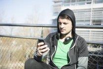 Людина в спортивному одязі з навушниками і смартфонів — стокове фото