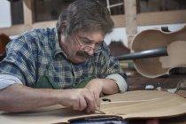 Craftsman carving violin — Stock Photo