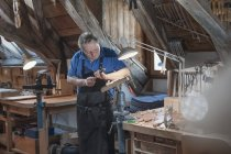 Craftsman carving at workshop — Stock Photo