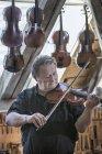 Craftsman testing violin — Stock Photo