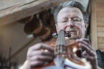 Handwerker begutachtet Geige — Stockfoto