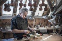Craftsman working at violin — Stock Photo