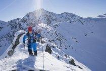 Skier walking on ridge of snow mountain — Stock Photo