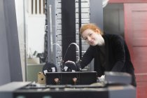 Женщина, стоящая у печатного станка — стоковое фото