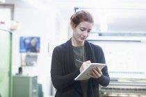 Worker preparing list at printing press — Stock Photo