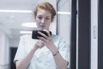 Enfermeira usando telefone celular no hospital — Fotografia de Stock