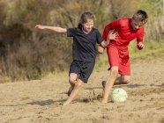 Menina e menino jogando futebol — Fotografia de Stock