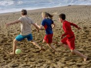 Girl and boys playing soccer — Stock Photo
