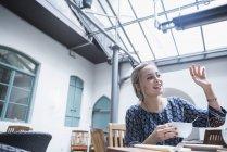 Frau, winken und halten Kaffeetasse — Stockfoto