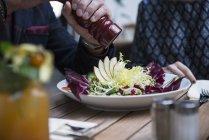 Человек приправы салат с перцем — стоковое фото