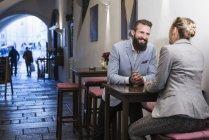 Coppia seduta sullo sgabello e che parla con una donna — Foto stock