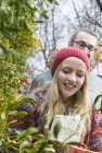 Couple with gifts and mistletoe twigs — Stock Photo