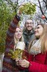 Друзі з подарунками і гілочки омели — стокове фото