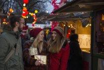 Друзья, стоя на Рождественский рынок — стоковое фото