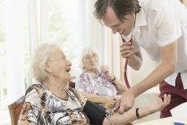 Zelador, verificação de pressão arterial da mulher sênior na casa de repouso — Fotografia de Stock