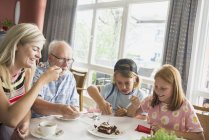 Grand-père avec petits-enfants manger le gâteau à table à l'intérieur de la maison — Photo de stock