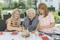 Family celebrating birthday of grandmother in rest home yard — Stock Photo