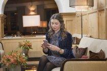 Femme utilisant un smartphone dans le hall de l'hôtel — Photo de stock