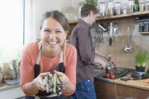Woman holding asparagus and smiling while preparing food with man — Stock Photo