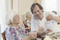 Custode guardando le foto con le donne anziane a casa di riposo — Foto stock