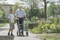 Boy helping grandfather walking with mobility walker at rest home park — Stock Photo