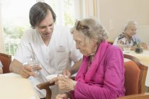 Caretaker giving medicine to senior woman at rest home — Stock Photo