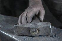 Close-up of blacksmith holding hammer — Stock Photo