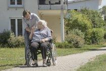 Fils marchant avec une mère handicapée en fauteuil roulant — Photo de stock