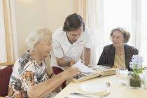 Caretaker watching photo album with senior women at rest home — Stock Photo
