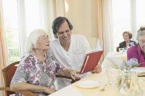 Zelador, lendo o livro com mulher sênior na casa de repouso — Fotografia de Stock