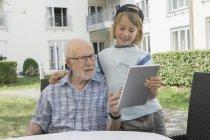 Hombre mayor con su nieto con tableta digital en patio de casa de descanso - foto de stock
