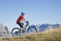Mountain biker riding on uphill in alpine landscape of Tyrol, Austria — Stock Photo