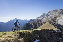 Mountainbiker fahren weiter bergan in alpiner Landschaft in Tirol, Österreich — Stockfoto