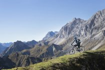Mountain biker admiring scenic view on mountain top, Tyrol, Austria — Stock Photo