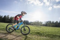 Little boy speeding on mountain bike on green meadow — Stock Photo