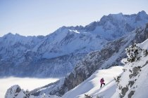 Woman in pink jacket climbing up ski slope, Bavaria, Germany, Europe — Stock Photo