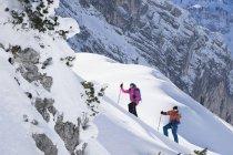 Couple climbing up ski slope in Upper Bavaria, Germany, Europe — Stock Photo