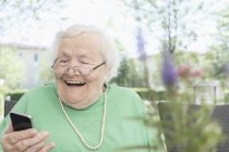 Senior woman using smartphone and laughing in garden — Stock Photo