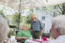 Couple de personnes âgées embrassant sur la table du petit déjeuner dans la maison de soins infirmiers — Photo de stock