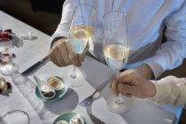 Vista recortada de un par de copas de champán tostadas en la mesa de la cena - foto de stock