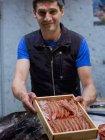 Vendeur de poisson présentant la boîte en bois avec crevettes au marché — Photo de stock