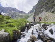 Man and woman crossing mountain stream in High Pyrenees, Cauterets, France — Stock Photo