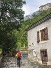 Randonneuse en passant par le vieux bâtiment dans le village de Gavarnie, France — Photo de stock