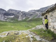 Female hiker admiring scenic view of Cirque de Troumouse from mountain hut, France — Stock Photo