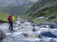 Woman crossing wild river in High Pyrenees near Cirque de Troumouse, France — Stock Photo