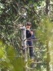 Девочка восхождение дерева и просматривая телескоп в Черном лесу, Фельдберг, Германия — стоковое фото