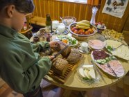Дівчина різати хліб під час сніданку в гірській Хатині — стокове фото